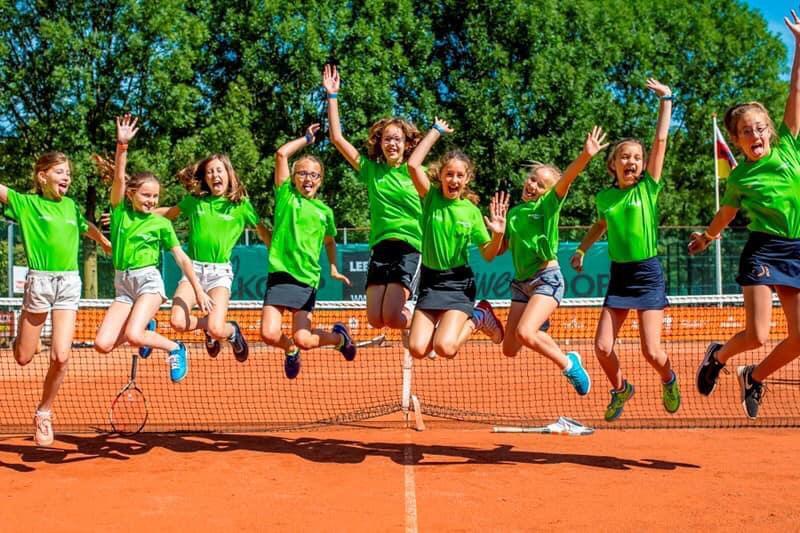 Kinderen springen in de lucht op het sportveld