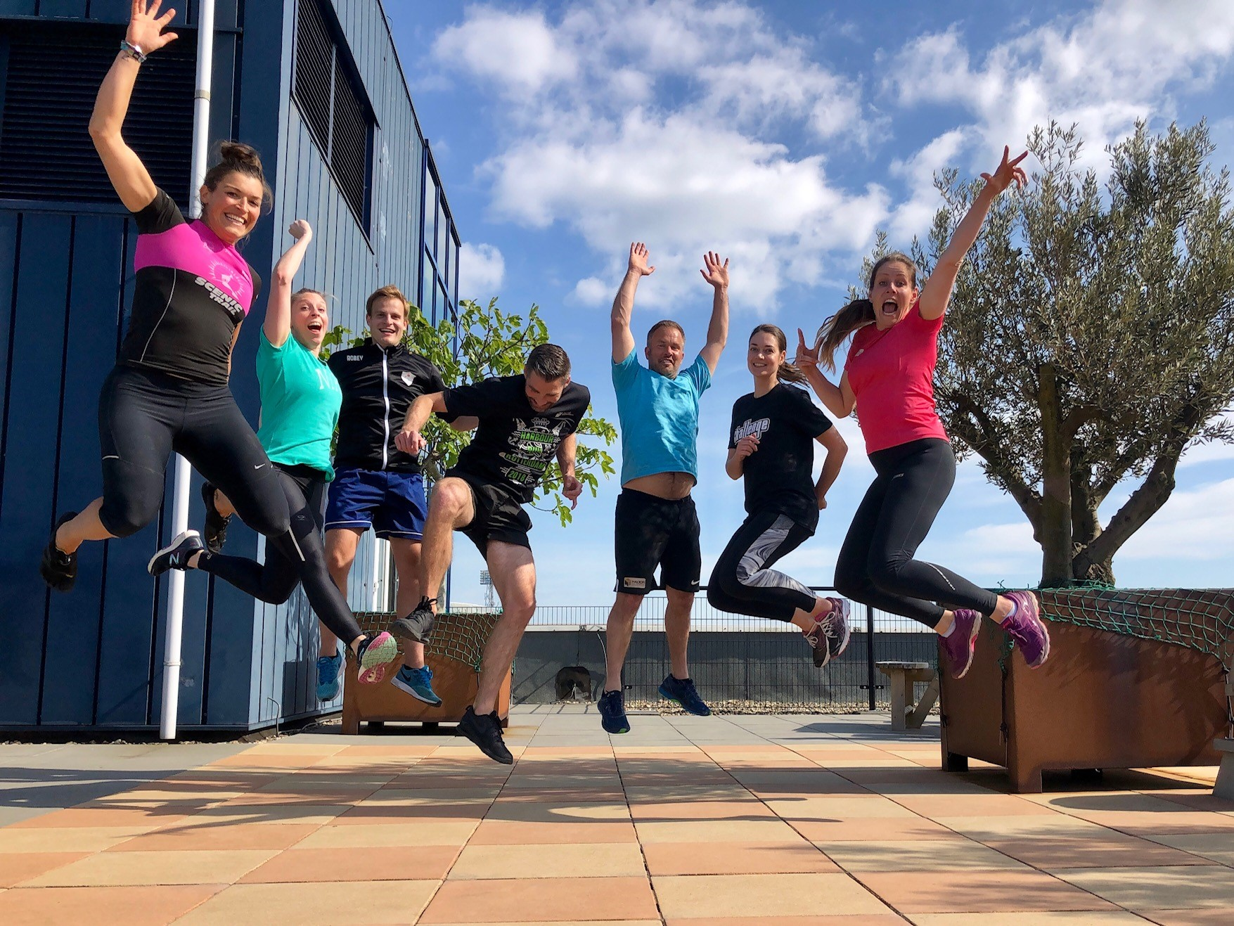 Sportende collega's springen blij in de lucht